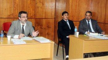 Gustavo Flores (centro), junto a su defensor, escucha el fallo.